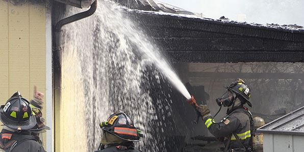 Crew of West Metro fighters putting water on a house fire.