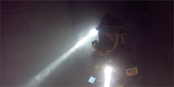 Firefighters training in a smoky room.